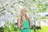 Beautiful cute blonde in a spring garden looking to the side — Stok fotoğraf