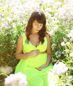 Pregnancy lovely woman in flowers in summer sunny day — Stock Photo
