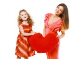 Bright stylish joyful mom and daughter in dress holding red hear — Stok fotoğraf