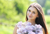 Lovely cute smiling girl with a bouquet of lilacs in summer — Stok fotoğraf