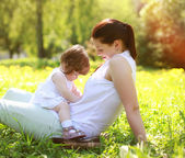 Mom and baby having fun on grass in the summer park — Stok fotoğraf