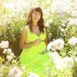 Pregnant lovely woman in flowers in summer sunny day — Stock Photo #53724365