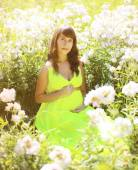 Pregnant lovely woman in flowers in summer sunny day — Stock Photo