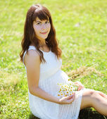Pretty pregnant woman with flowers on the grass summer — Stock Photo