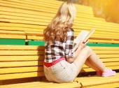 Young girl sitting reading a book on the bench in city park in s — Stock Photo