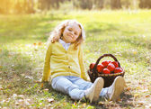 Little girl with autumn basket and apples outdoors — Stock Photo