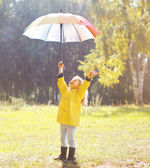 Positive child with colorful umbrella having fun in autumn day — Stock Photo