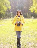 Pretty woman with retro camera in sunny autumn day — Stock Photo