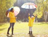 Family with colorful umbrella having fun enjoying weather in aut — Stock Photo