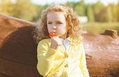 Little child with sweets having fun outdoors — Stock Photo