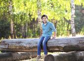 Young joyful boy teen brunette sitting on the log  — Stock Photo