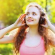 Summer fun lifestyle portrait young girl with headphones listeni — Stock Photo #53777391
