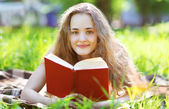 Young happy girl reading a book lying in a park in sunny summer  — Stock Photo
