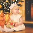Christmas, magic, people concept - happy baby with gift near chr — Stock Photo #54529007