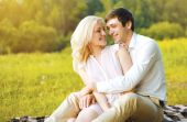Happy pretty couple in love having fun outdoors on the grass  — Stock fotografie