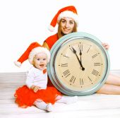 Christmas and people concept - mother with child and clock — Stock Photo