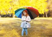 Positive cute child with colorful umbrella in autumn day — Foto de Stock