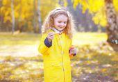 Little positive child having fun outdoors in autumn park — Stock Photo