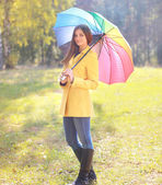 Beautiful woman with colorful umbrella outdoors in autumn day — Fotografia Stock