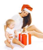 Jul och människor koncept - lycklig mamma i santa hatt och chi — Stockfoto