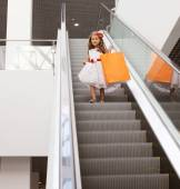 Little girl in dress with shopping bag in mall — Foto de Stock