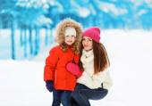 Happy mother with child in winter snowy day — Stock Photo