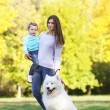 Young mother and child walking with white Samoyed dog in the par — Stock Photo #63130773