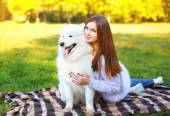 Pretty happy woman and dog outdoors in the park — Stock Photo