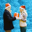 Christmas and people concept - happy man giving a box gift to a — Stock Photo #63816641
