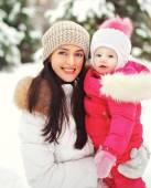 Portrait of a happy mother with child outdoors in the winter day — Stockfoto