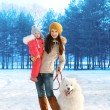 Happy mother and child walking with white Samoyed dog in winter — Stock Photo #72357489