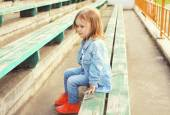 Portrait of stylish little girl child in the jeans clothes sitti — Stockfoto