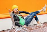 Fashion blonde woman riding having fun in shopping trolley cart — Stock Photo