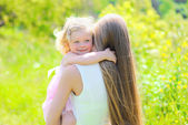 Sunny portrait of happy child hugging mother in summer day — Stock Photo
