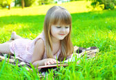 Portrait of little smiling girl child reading a book lying on th — Stock Photo