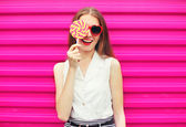 Sweet pretty young woman having fun with lollipop over pink back — Stock Photo
