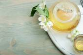 Jasmine tea in a glass tea pot on blue wooden background  — Stok fotoğraf
