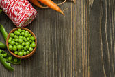 Raw carrots, green peas and red twine on wooden table  — Foto Stock