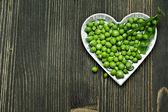 Green peas in bowl on dark wooden background — Stok fotoğraf