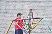 Boy with his father at the playground near the brick wall — Stock Photo