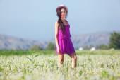 Model in a pink dress on a dandelion field in a straw hat — Foto de Stock