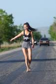 Hitchhiking model posing on motorway  — Stock Photo