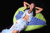 Girl posing in the style of rock lying on bean bag — Stock Photo
