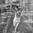 Cheerful girl dancing under jets of water in city fountain — Stock Photo