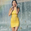 Girl in a slinky dress with long hair in water droplets in the city fountain — Stock Photo #53963383
