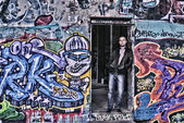 A man stands in the doorway on the background of painted wall graffiti — ストック写真