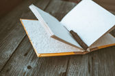 Notepad with pencil on wooden table (vintage color toned image) — Stock Photo