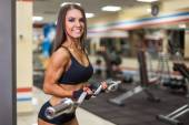 Bodybuilder girl with barbell in gym — Stok fotoğraf