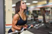 Bodybuilder girl with barbell in gym — Stock Photo