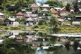 Die Reflexion. Das alte Dorf am Ufer des Teiches. — Stockfoto